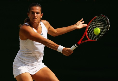 WIMBLEDON, ENGLAND - JUNE 27:  Amelie Mauresmo of France plays a backhand during the women's singles third round match against Flavia Pennetta of Italy on Day Six of the Wimbledon Lawn Tennis Championships at the All England Lawn Tennis and Croquet Club on June 27, 2009 in London, England.  (Photo by Ian Walton/Getty Images)